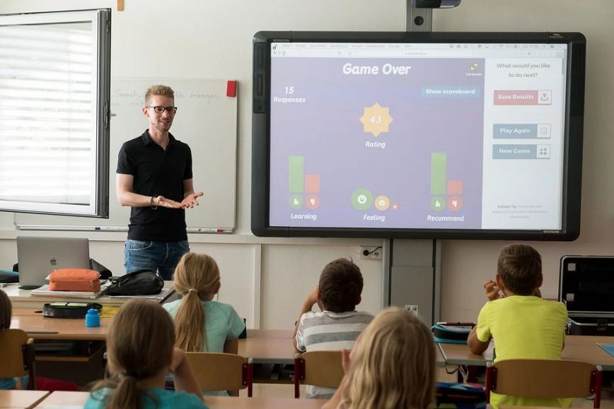 A teacher standing in front of his students, discussing his lessons flash on a screen